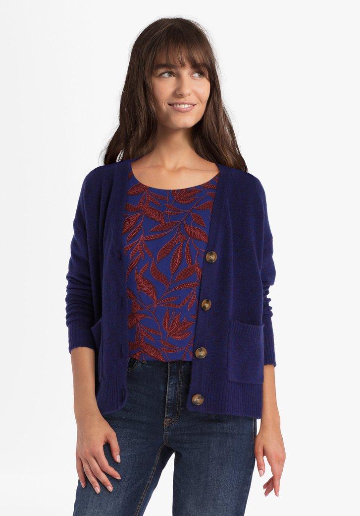 Cardigan bleu en tricot avec une teinte rouge