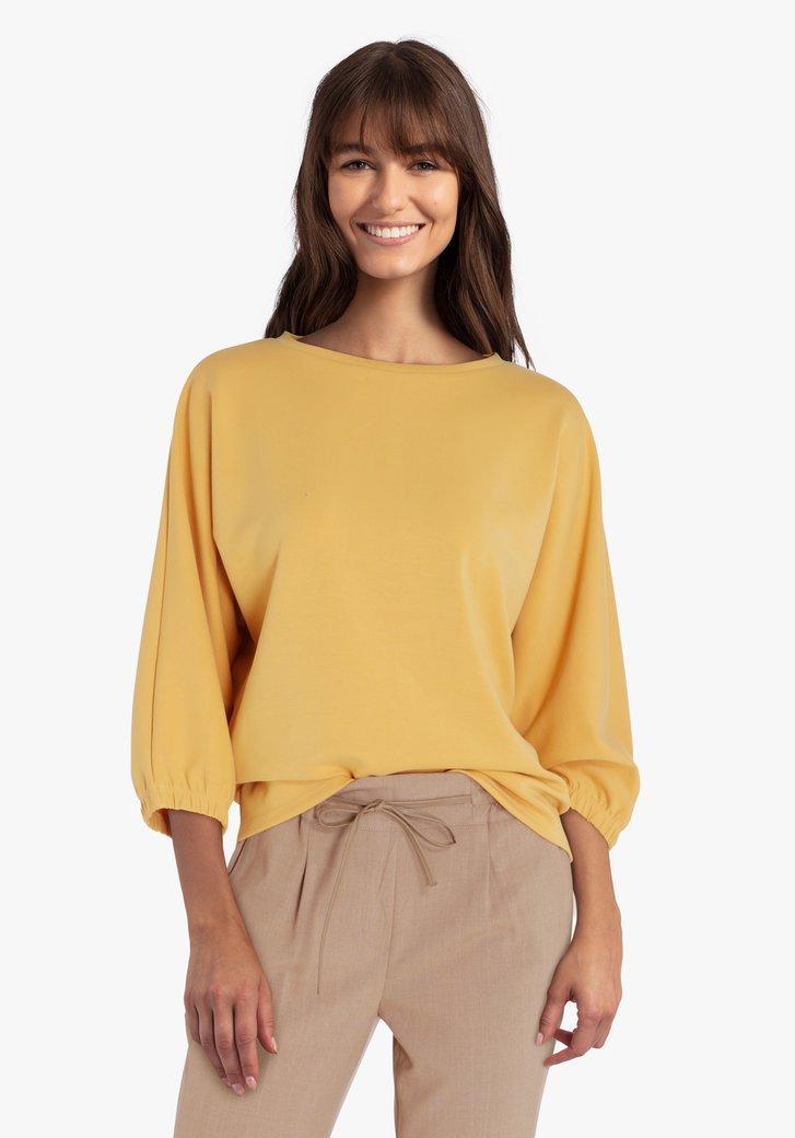 Goudgele trui met elastiek aan de mouwen