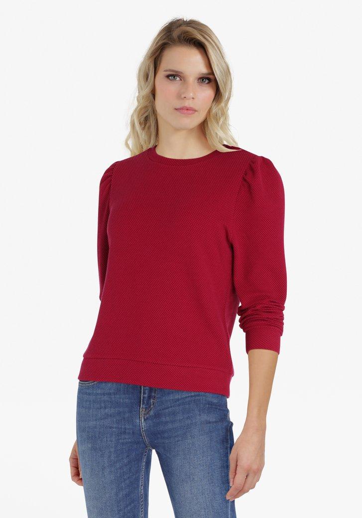 Rode trui met accentmouwen